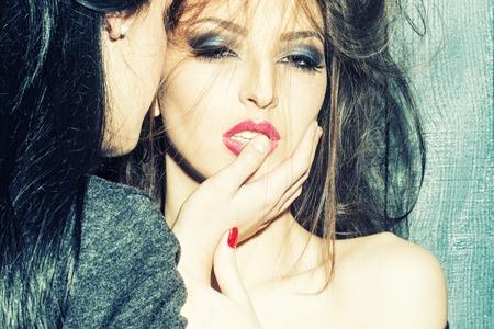 herrin: Nahaufnahme von zwei schöne sinnliche junge Brünette Mädchen Herrin mit nackte Schulter und Hand in den Mund umarmen und küssen Nähe stehenden Wand Innen im Studio, horizontale Foto