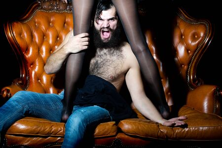 hairy legs: One handsome serious young adult man with long black lush beautiful beard moustache and bare hairy chest sitting on leather couch with sexy female legs in stockings indoor, horizontal picture