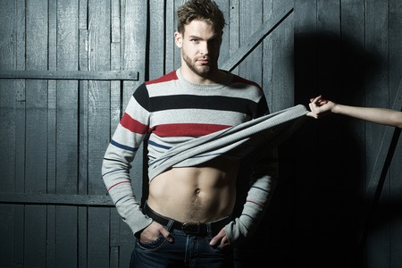 undressing: One sexual young stylish handsome muscular lover macho man with beard in sweater with bare torso and female mistress hand undressing him standing indoor in studio on wooden backdrop, horizontal photo Stock Photo