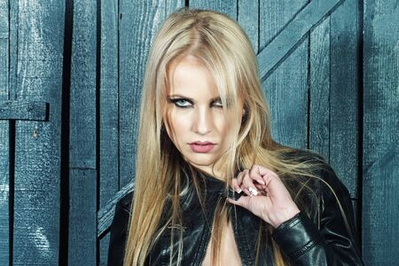 sexy blonde girl: Portrait of one beautiful sensual sexy young serious passionate blonde woman with long hair in leather black jacket in studio on wooden wall background, horizontal picture