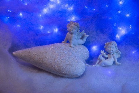 soulful: Closeup of beautiful soulful figurine composition of cupid angels for valentine day or christmas with small pillow in shape of heart lying on white wadding decorating snow with bright light sparks