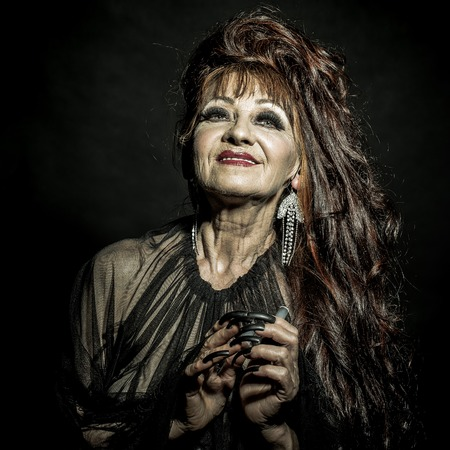 One old scary smiling witch woman with long red knotty hair in blouse with black long nails on hand as halloween character with bright makeup in studio on black background, square photo Standard-Bild