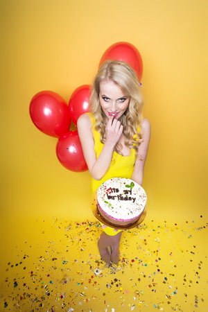 One pretty emotional young flirtatious blonde girl with long curly hair holding birthday cake with candles near bunch of red balloons with confetti indoor in studio on yellow backdrop, vertical photo