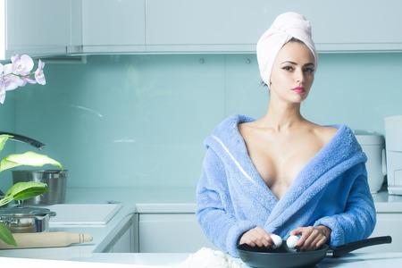 cabeza femenina: Una ama de casa hermosa mujer sensual sexual en azul bata de toalla y un turbante toalla en la cabeza con los hombros desnudos de pie en el desayuno de cocina cocina de huevos fritos en la vida de la mañana, horizontal Foto de archivo