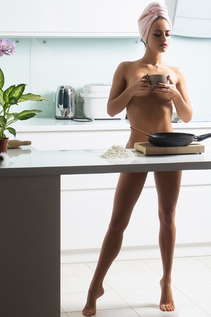 One sexy pretty sensual naked female housewife in terry towel turban on head with straight bare body and legs standing in kitchen cooking breakfast with coffee cup in morning life, horizontal photo