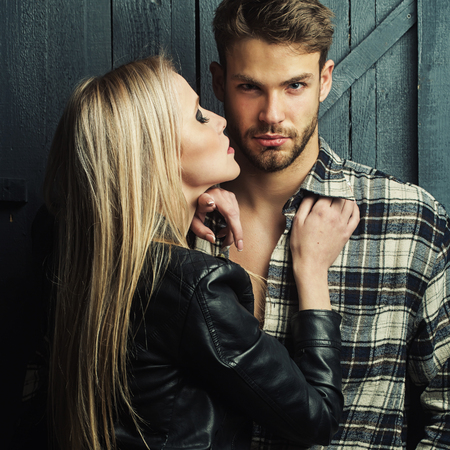 breast beauty: Young sexual couple of pretty blonde woman in leather jacket standing near handsome serious man in checkered shirt with bare muscular chest in studio on wooden background, square picture Stock Photo