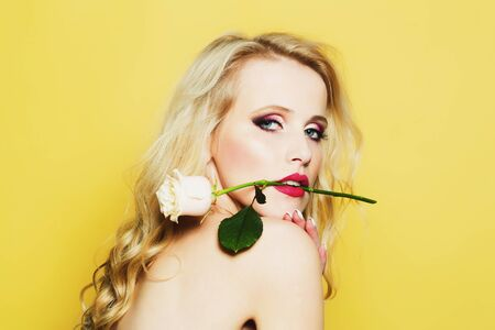 brigt: Closeup portrait of one beautiful sexy passionate blonde woman with long curly hair in studio with bare shoulder and brigt makeup holding rose flower in mouth on yellow backdrop, horizontal picture
