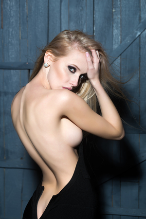 nude girl pretty young: Back view of one sexual attractive slender blonde woman with flexible straight body undressing standing in black dress in studio on wooden wall background, vertical picture