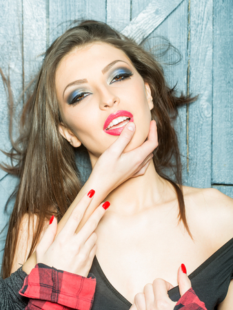 herrin: Portrait of one pretty sensual stylish young brunette girl with female mistress hand in mouth in black underwear and checkered red shirt with bare shoulder standing indoor in studio, vertical photo Lizenzfreie Bilder