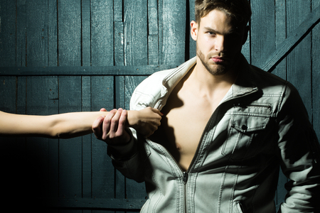 undressing: One sexy young stylish handsome muscular lover macho man with beard in jacket with bare chest and female mistress hand undressing him standing indoor in studio on wooden backdrop, horizontal photo Stock Photo