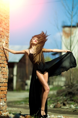 Full length view of one straight slim beautiful sensual romantic pretty young woman in long black evening dress with bare legs outdoor suuny windy day near brick wall on blue sky backdrop, vertical