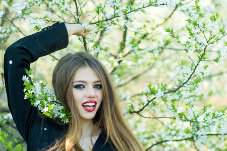 One sensual sexy pretty strange smiling young woman with long hair in black jacket with red lips standing outdoor in blooming tree banches suuny day on natural background, horizontal picture
