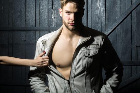 nackte brust: Eine sexy junge stilvolle sch�nen muskul�sen Liebhaber Macho Mann mit Bart in der Jacke mit nackten Brust und weibliche Geliebte Hand Auskleiden ihn im Studio Innen stehen auf h�lzernen Hintergrund, horizontal Foto