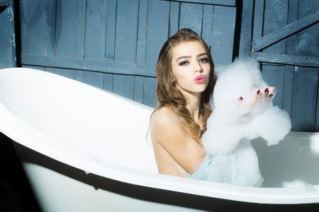 relaxion: One beautiful sensual playful flirtatious young woman with long hair in blue knitted cloth sitting in white bath tub playing with soap foam indoor on wooden background, horizontal picture Stock Photo