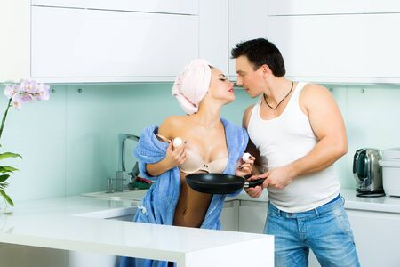 woman cooking: Sexy young family kissing couple of woman in blue terry dressing gown and towel turban on head and muscular handsome man undressing her standing in kitchen cooking breakfast, horizontal picture Stock Photo