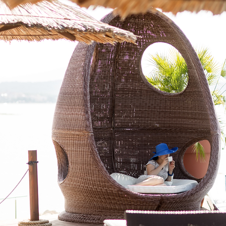 day bed: Photo of girl in blue hat drinking coffee relaxing in rattan beach hut egg-shaped summer day bed couch with flock and cushions for sun protection lounge on exotic background, square picture