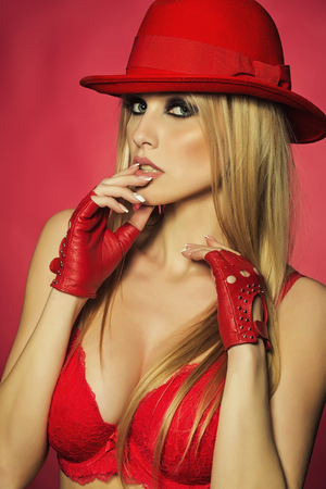 One attractive sexual sensual young blonde woman with long hair in red cowboy hat gloves and bra as strip dancer on pink backdrop, vertical picture