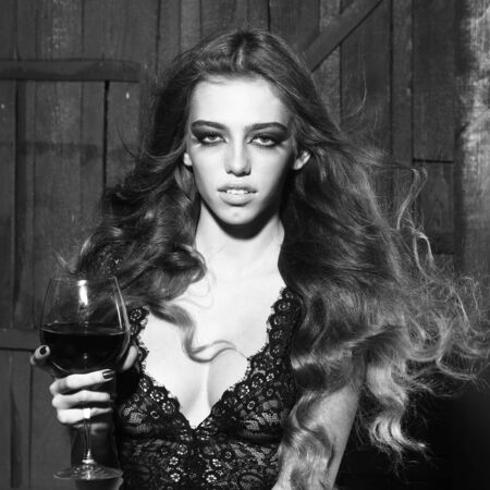 black smoke: One beautiful enigmatic sexy young fashionable sensual girl with long curly hair bright makeup in black cloth holding wine glass with liquid with smoke black and white, square picture