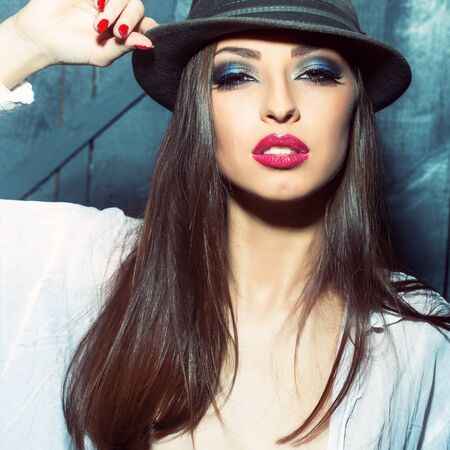 sexual relations: One attractive sensual fashionable young brunette pensive woman with bright makeup and beautiful hair in white blouse holding hat with hand in studio on wooden wall background, square picture