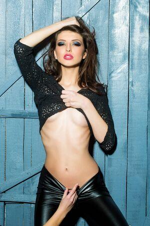 herrin: Eine attraktive sexy stilvolle junge Frau mit hellen Make-up und nacktem Oberkörper in schwarzer Unterwäsche und Leder tausers mit weiblichen Herrin Hand im Studio auf Holzwand Hintergrund, vertikale Foto