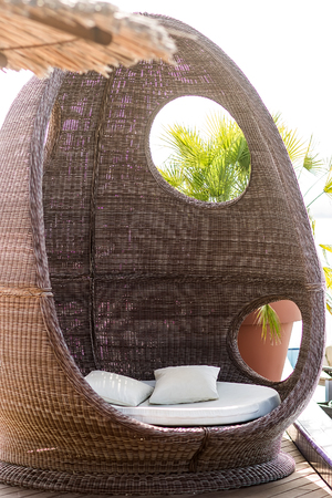 sun protection: Photo closeup of rattan beach hut egg-shaped summer day bed couch with flock and cushions for sun protection lounge relaxing atmosphere on exotic background, vertical picture Stock Photo