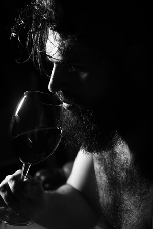 hairy: Closeup side view of one handsome sad pensive young adult man with long black lush beautiful beard and moustache holding glass with red wine indoor on blurred background, vertical picture Stock Photo