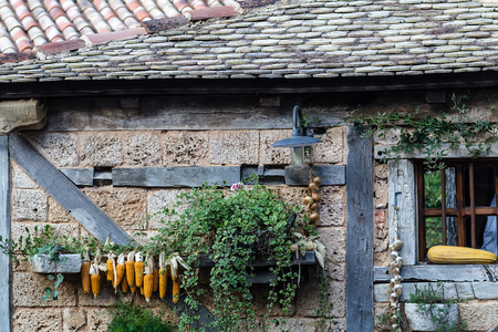 countrified: Photo closeup of aged stone cottage with hand-molded tile roof small wooden window lamp green plants bunches of corns ropes of onion garlic and squash on countrified background, horizontal picture