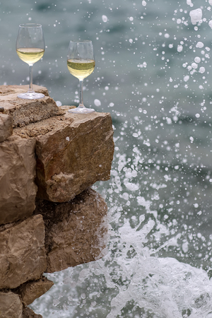 half full: Photo closeup of two half full tall wine glasses standing on stone at seashore in splashes spindrifts silhouetted against blue sea at day time over blurred seascape background, vertical picture Stock Photo