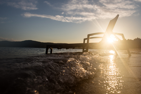 chaise lounge: Photo closeup with sun spot of chaise lounge day bed couch for sun bath relaxing atmosphere standing in sea water waves hit at seashore silhouetted against seascape background, horizontal picture