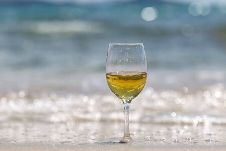 half full: Photo closeup of one half full tall wine glass standing on sand at seashore silhouetted against blue sea at day time over blurred seascape background, horizontal picture