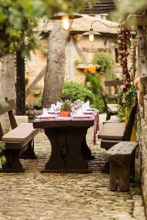 settles: Photo closeup of aged rustic timber settles and table set with porcelain flat plates embroidered tablecloth flatware wooden cutlery glasses in cottage yard on rural background, horizontal picture Stock Photo