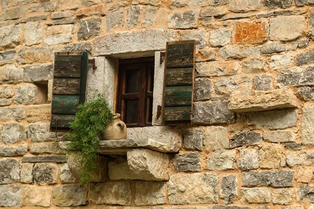unpainted: Photo closeup outdoor flower pot and open old wooden window with aged timber unpainted peeled shutters against stone facade wall for privacy and defense on masonry background, horizontal picture Stock Photo