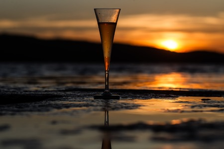 beach scene: Photo closeup of one full champagne flute glass standing on wet stone at seashore silhouetted against sunset light over blurred dusk background, horizontal picture Stock Photo