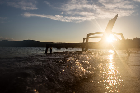 day bed: Photo closeup with sun spot of chaise lounge day bed couch for sun bath relaxing atmosphere standing in sea water waves hit at seashore silhouetted against seascape background, horizontal picture