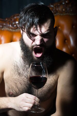 hairy: Closeup view portrait of one handsome screaming emotional young adult man with long black lush beautiful beard and moustache holding glass with red wine indoor on blurred background, vertical picture Stock Photo