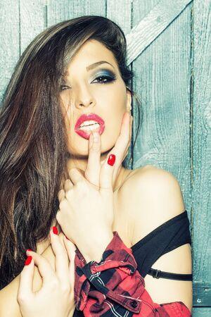 herrin: Portrait von einem ziemlich sinnlich stylish junge brünette Mädchen mit weiblichen Geliebten Hand in den Mund in schwarzer Unterwäsche und karierten roten Hemd mit nackte Schulter stehend Innen im Studio, vertikale Foto