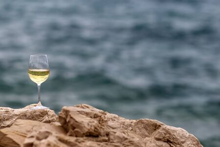 half full: Photo closeup of one half full tall wine glass standing on stone at seashore silhouetted against blue sea at day time over blurred seascape background, horizontal picture