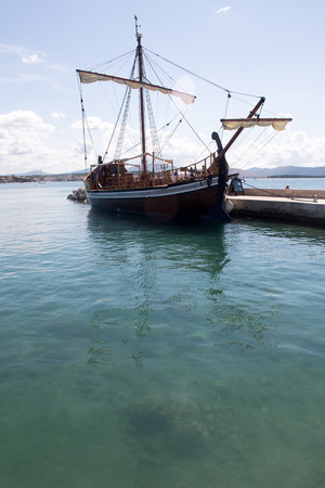 shorten: Photo closeup of one beautiful wooden antiquated sailing-ship with shorten sails lies idle in dry dock at seashore silhouetted against blue sea at day time over seascape background, vertical picture Stock Photo
