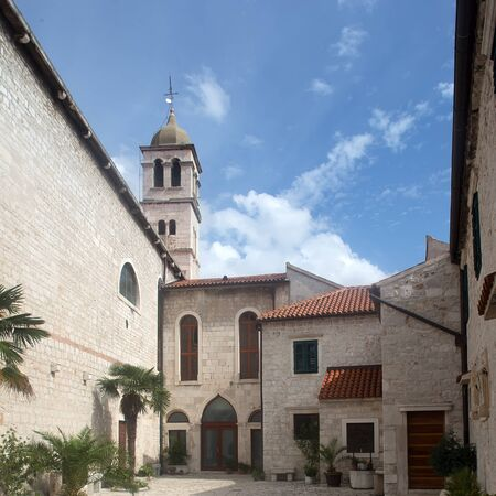 townscape: Photo closeup of medieval inner yard old white stone church against blue sky day time on townscape background, square picture