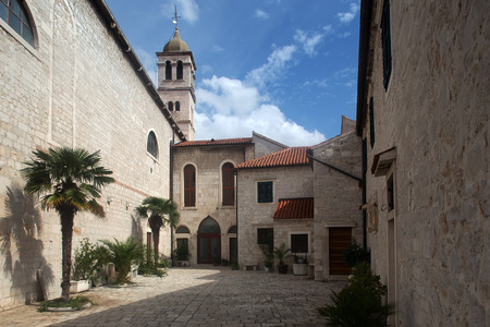 day time: Photo closeup of medieval inner yard old white stone church against blue sky day time on townscape background, horizontal picture