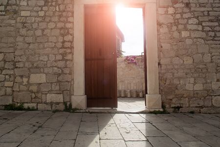 townscape: Photo closeup with sun spot of medieval inner yard old white stone architecture door open doorway with daylight day time on townscape background, horizontal picture Stock Photo