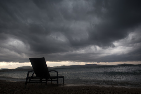 chaise lounge: Photo closeup of one chaise lounge day bed standing on pebbles on beach  at dusk low dark clouds bad weather grey sea shore against seascape background, horizontal picture