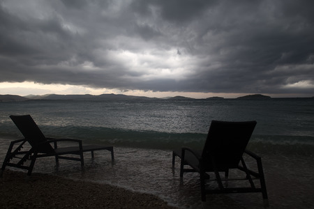 lounges: Photo closeup of two chaise lounges day beds standing on pebbles on beach at dusk low dark clouds bad weather grey sea shore against seascape background, horizontal picture