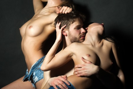 Sex: Three young sexy people of handsome bearded muscular macho man touching two sensual attractive girls lovers with beautiful body and naked chest close to each other indoor, horizontal picture