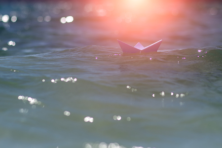 Photo closeup with sun spot one white paper origami boat riding on blue salt sea waves ocean water surface with ripples on blurred seascape background, horizontal picture Stock Photo