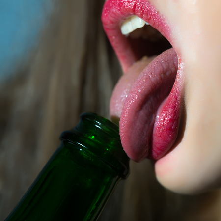 Closeup view of female facial body part of sexual lips with bright red lipgloss licking with tongue in open mouth green color glass wine bottle on blurred background, square picture Stock Photo