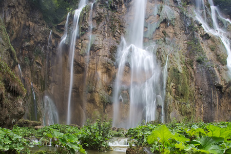 falling down: Photo of beautiful waterfalls cascades falling down from mountain wall rock surrounded by picturesque green rich foliage on natural landscape background, horizontal picture