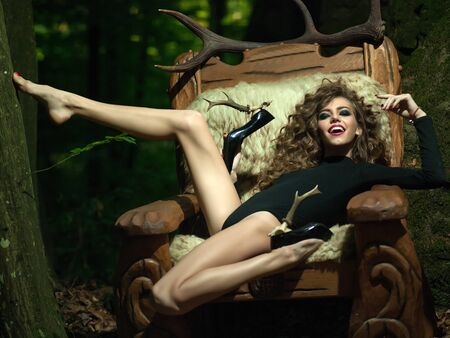 woodsy: One beautiful young flexible sensual girl with long curly hair bright makeup and straing slim body in black underwear and shoes with heel of antlers sitting in big wooden arm chir with fur in forest Stock Photo