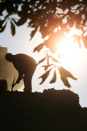 pickaxe: Labour man with hard tool moil pick-axe working at deconstructing of building male physical job outdoors on natural background of silhouette of branch chestnut tree and bright sunbeam, vertical photo Stock Photo