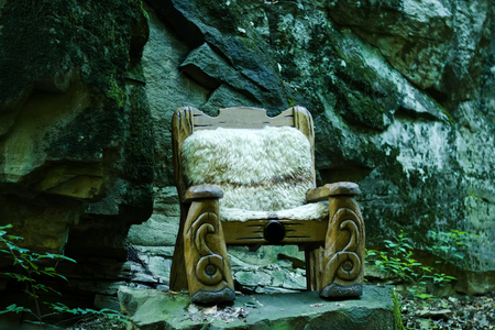 standing stone: One big wooden cut beautiful arm chair as forest queen fairytale throne standing in wood with no people outdoor on grey stone natural background, horizontal picture Stock Photo